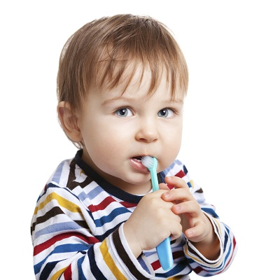 Baby in striped shirt holding toothbrush in mouth
